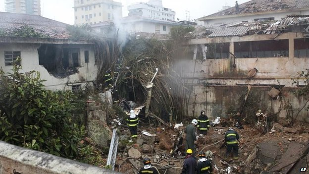 Firefighters work where a private jet carrying Brazilian presidential candidate Eduardo Campos crashed in Santos on 13 August, 2014.