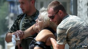 Injured woman is helped in Donetsk