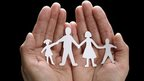 A paper chain in the form of a family of four holding hands
