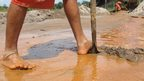 close up of man's bare legs and feet in brown water, digging the mine