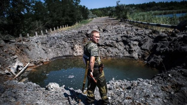 A pro-Russian gunman next to a bomb crater near Donetsk (14 August 2014)