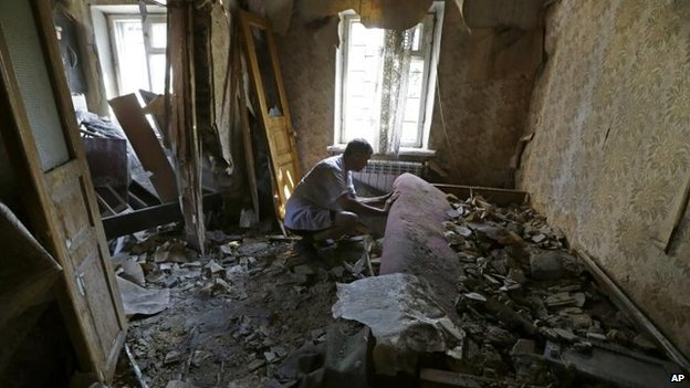 A resident of Donetsk inspects shell damage (14 August 2014)