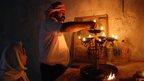 Candle lighting at a Yazidi home shrine