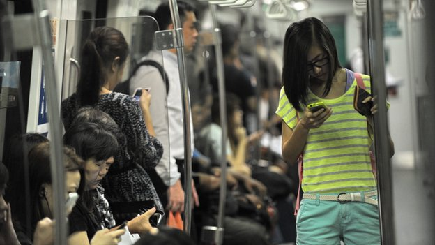 People checking phones on Singapore train