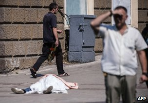 A body lies covered on a street of Donetsk, 14 August