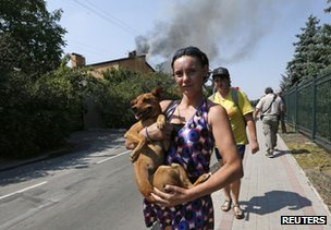 A woman carries a dog after shelling through a street in Donetsk, 14 August
