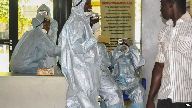 Nigerian health workers in protective clothing wait in an emergency ward as preparation for receiving any emergency Ebola patients at the National Hospital in Abuja, Nigeria (12 August 2014)