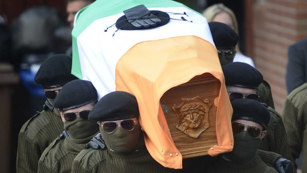 The masked men carried Tony Catney's coffin during the service on Wednesday
