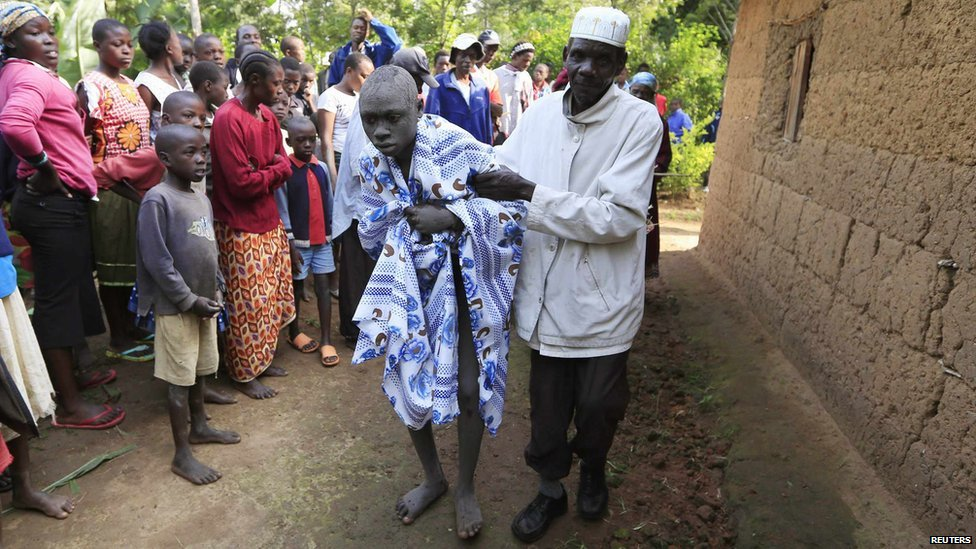 A boy who just underwent circumcision is assisted by his uncle outside their home after undergoing the rite of passage ritual currently taking place in Kenya's western region of Bungoma on 9 August 2014