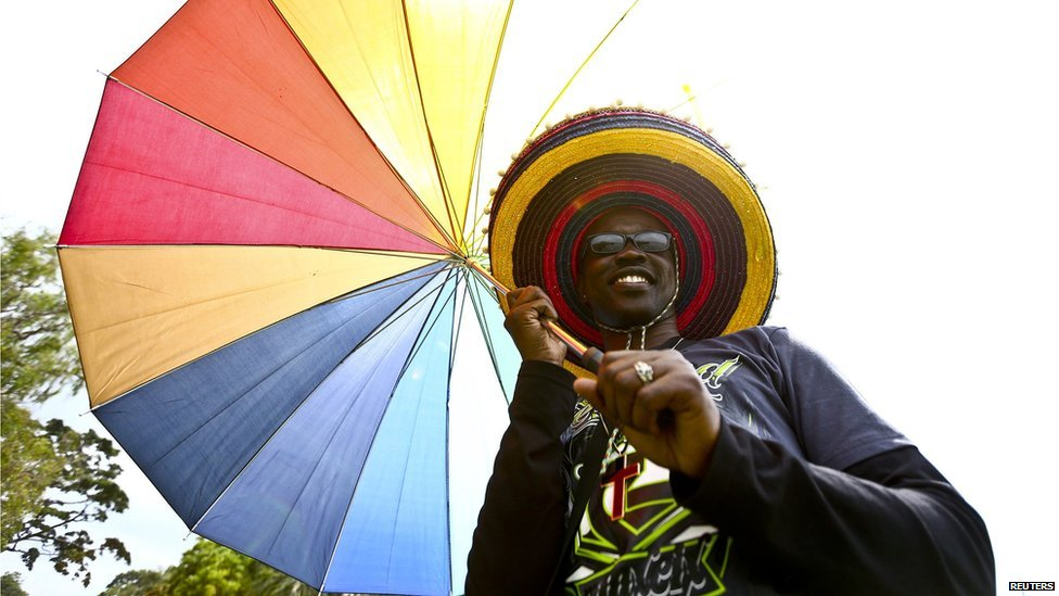 A man poses for pictures with an umbrella while celebrating the annulment of an anti-homosexuality law by Uganda's constitutional court in Entebbe on 9 August 2014