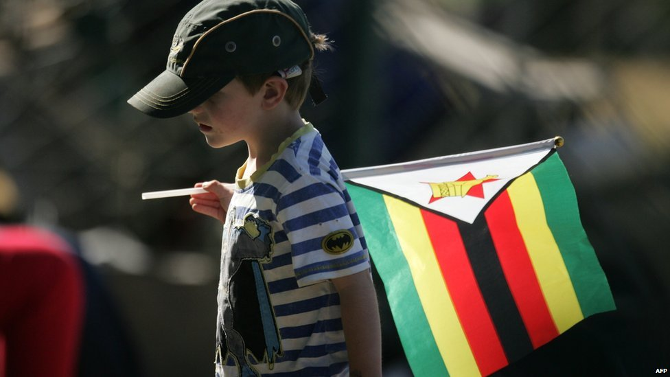 A young Zimbabwe cricket fan carries his country's flag during the first day of a test match between South Africa and hosts Zimbabwe at the Harare Sports Club, on 9 August 2014
