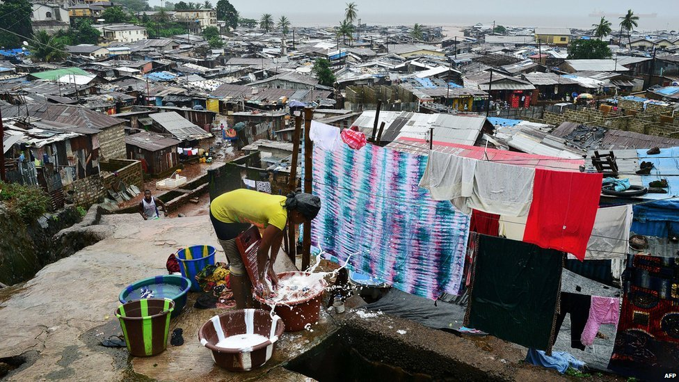 A woman washes clothes in the Kroo town slum in Freetown, Sierra Leone, on 13 August  2014