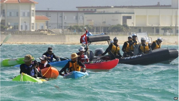 Anti US base protesters in canoe are blocked by a Japan Coast Guard speed boat in Nago, Okinawa, southern Japan, Thursday, 14 Aug 2014