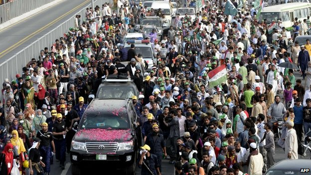 Supporters of Canada-based preacher Tahir-ul-Qadri escort a vehicle carrying Qadri in Pakistan's eastern city of Lahore on August 14, 2014