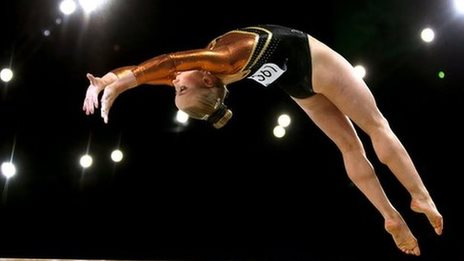 Women performing a back flip from the beam