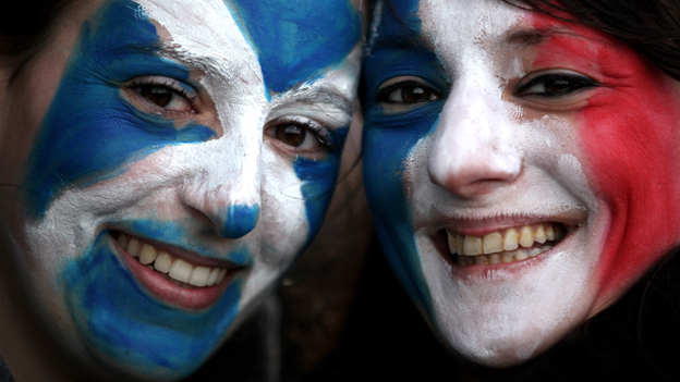 Two people face-painted with Scottish and French flags