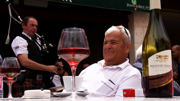 A glass of wine at a table with a bagpipe-playing man behind