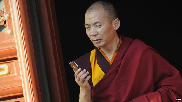 A Buddhist monk in Beijing checks his mobile phone