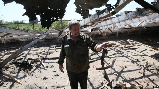 A local man holds a part of a rocket at the site of an explosion in Donetsk