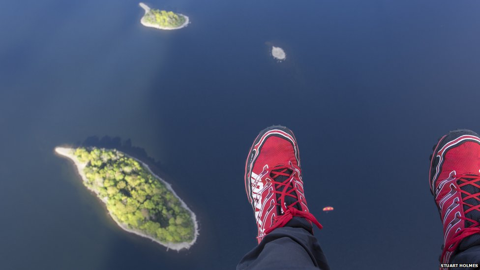 A paraglider's feet above a lake