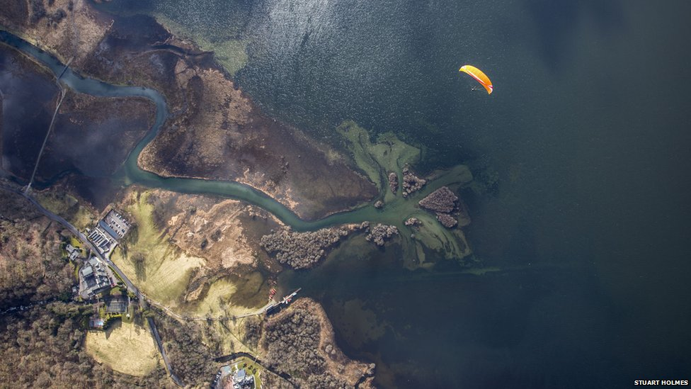 A paraglider flies over a lake