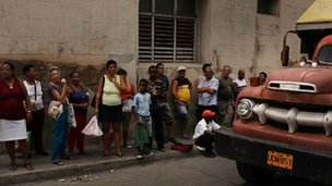 People queue for food outside a government store in Cuba (in 2012)