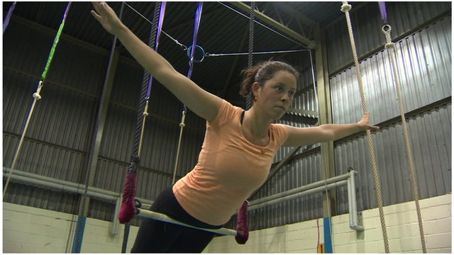A woman balances on a trapeze with her arms both pointing out