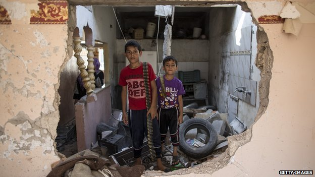 Two children stand in their demolished home holding ammunition on August 14, 2014 in Beit Hanoun, Gaza