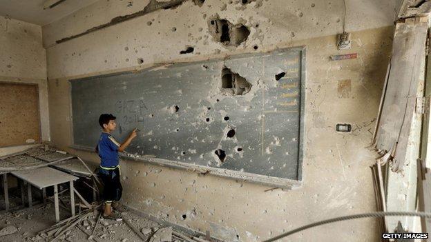 A Palestinian boy writes on a shrapnel riddled backboard at Sobhi Abu Karsh school in Gaza City