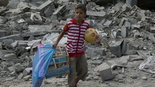 A Palestinian child carries a ball and bird cage