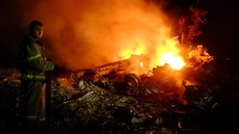 A firefighter stands across the debris of MH17