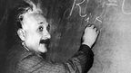 Albert Einstein writing an equation on a blackboard