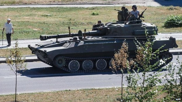 A pro-Russian militia tank moves along a street in Donetsk, 15 Aug
