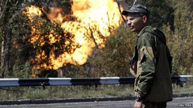 A pro-Russian rebel looks on as a gas pipeline is ruptured by shelling in Donetsk, 15 Aug