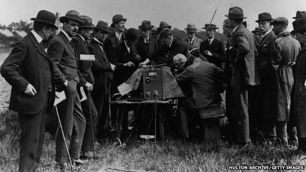 1st June 1919: A group of men crowd round the Marconi wireless telephony fields installation, presumably listening for news of developments as the end of World War I approached. (Photo by Hulton Archive/Getty Images)