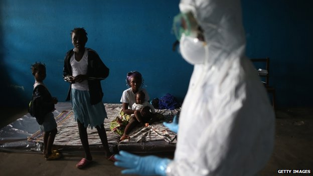 Health worker speaks with families in classroom used as Ebola isolation ward in Monrovia, Liberia. 15 Aug 2014