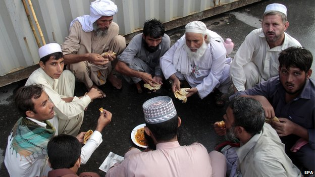 Supporters of Tahirul Qadri, a Pakistani-Canadian cleric, have a meal after they arrived to attend a protest march in Islamabad, Pakistan, 16 August 2014