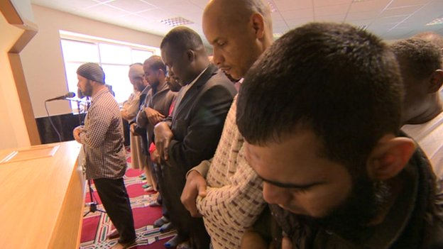 Mourners bowing their heads in front of a coffin