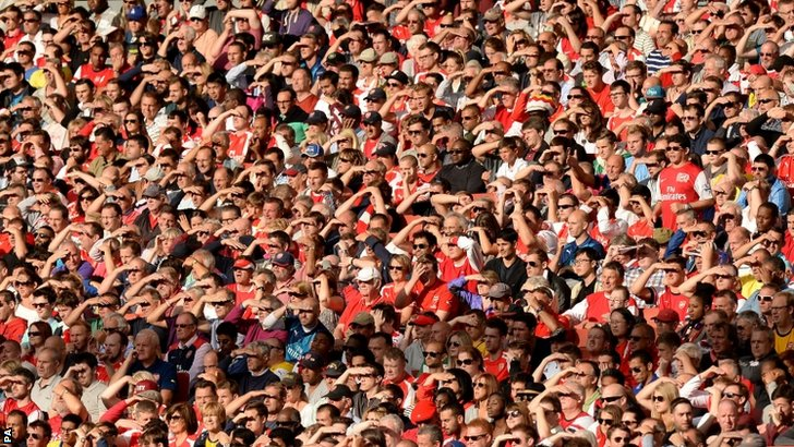 Arsenal fans shield their eyes from the late evening sun