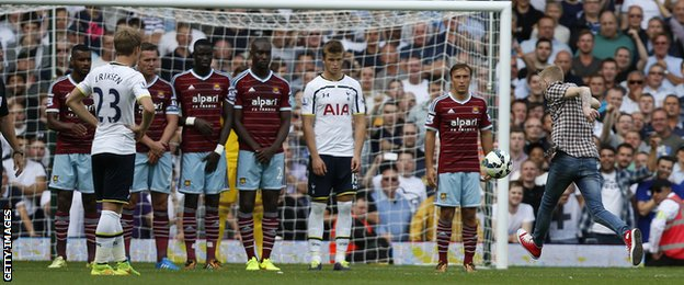 A fan, who has invaded the pitch, takes a free-kick in the West Ham v Tottenham game