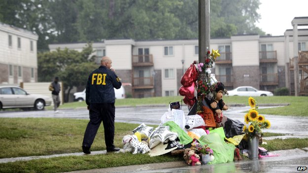 An FBI agent walks past a memorial to Michael Brown at the location where he was killed in Ferguson, Missouri - 16 August 2014
