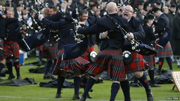 Members of the Field Marshall Montgomery Pipe Band react to winning the annual World Pipe Band Championships at Glasgow Green