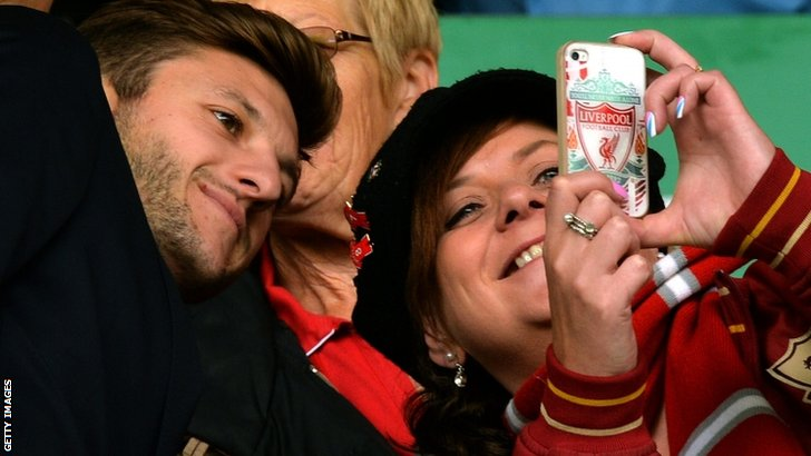Liverpool's English midfielder Adam Lallana poses for a picture with a supporter