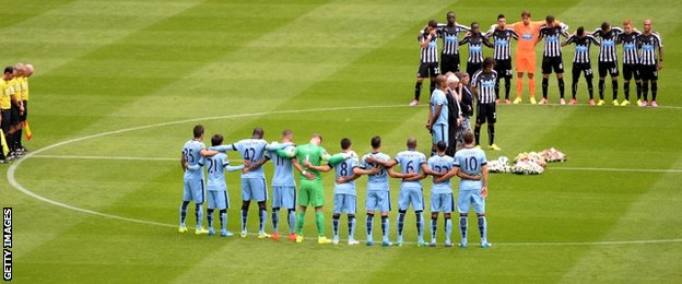 Manchester City and Newcastle United players gather in the centre circle to pay tribute along with the crowd at St James' Park to Magpies fans Liam Sweeney and John Alder