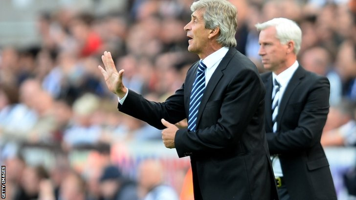 Manuel Pellegrini the Manchester City manager instructs his players as Alan Pardew the Newcastle manager looks on