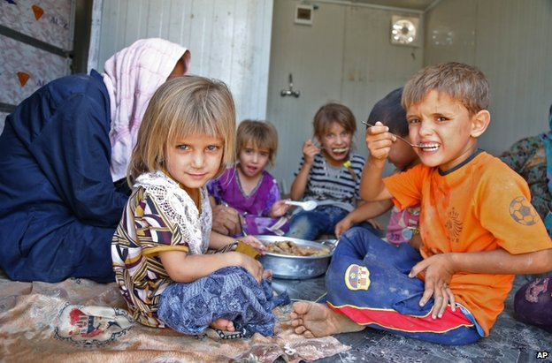Shia Muslim refugees from Mosul eat at a refugee camp in Baghdad, 17 August