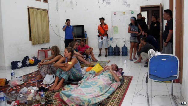 Survivors rest at a house near to the Indonesian town of Bima on 17 August, 2014 after being rescued when their tourist boat sank