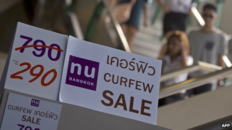 Tourists walk past discount promotion placards displayed at a shop in Bangkok