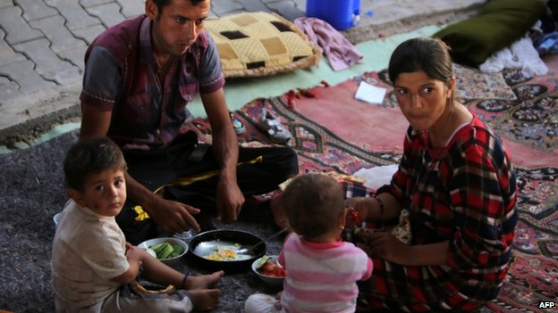 A displaced Iraqi family from the Yazidi community eat under a bridge where they found refuge after Islamic State (IS) militants attacked the town of Sinjar on 17 August 2014
