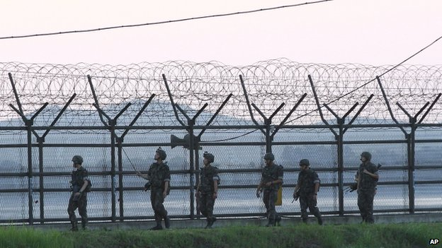 South Korean soldiers patrol the wire fences near the demilitarised zone between the two Koreas in Paju, South Korea, on 4 July 2014